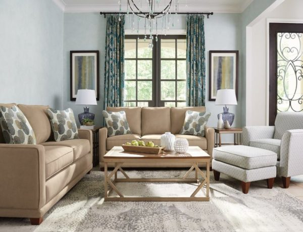 Grey living room with brown couches and a white chair